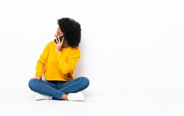 Junge afroamerikanische frau, die auf dem boden sitzt und ein gespräch mit dem mobiltelefon mit jemandem hält