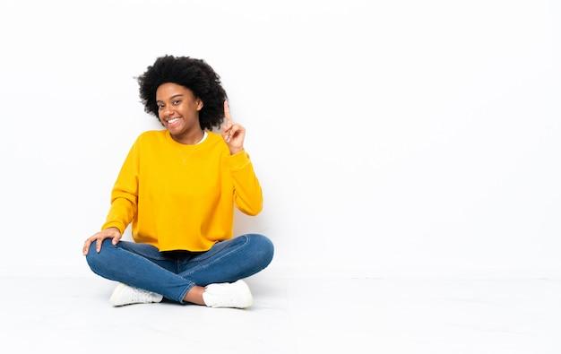 Junge afroamerikanische frau, die auf dem boden sitzt und einen finger im zeichen des besten zeigt und hebt