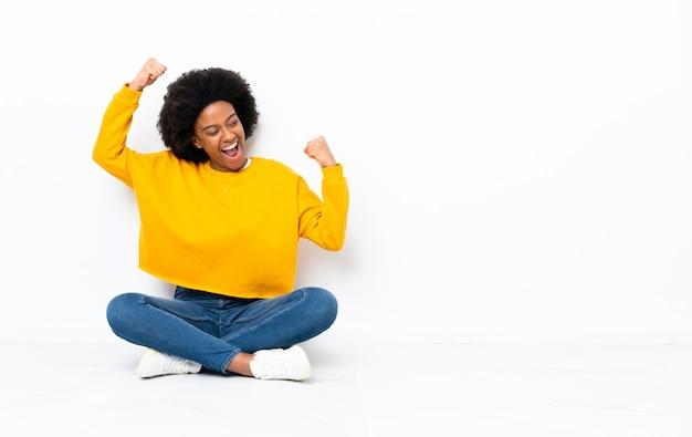 Junge afroamerikanische frau, die auf dem boden sitzt und einen sieg feiert
