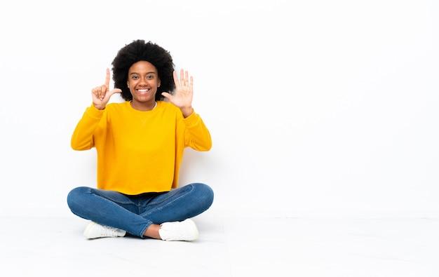 Junge afroamerikanische frau, die auf dem boden sitzt und sieben mit den fingern zählt