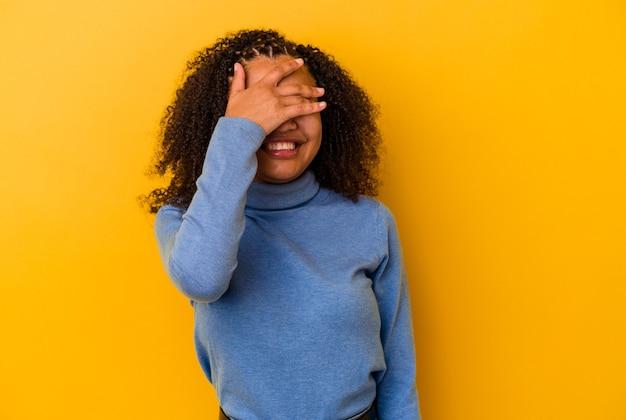 Junge afroamerikanische frau, die auf gelbem hintergrund isoliert ist, bedeckt die augen mit den händen, lächelt breit und wartet auf eine überraschung.