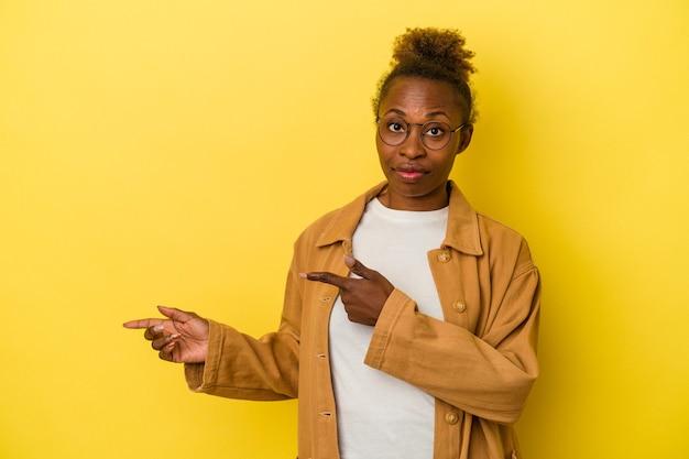 Junge afroamerikanische frau, die auf gelbem hintergrund isoliert ist, schockiert und zeigt mit zeigefingern auf einen kopienraum.