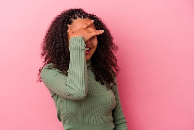 Junge afroamerikanische frau, die auf rosafarbenem hintergrund isoliert ist, bedeckt die augen mit den händen, lächelt breit und wartet auf eine überraschung.