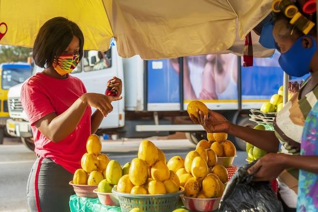 Junge afroamerikanische frau, die beim einkaufen auf einem obstmarkt eine schützende gesichtsmaske trägt