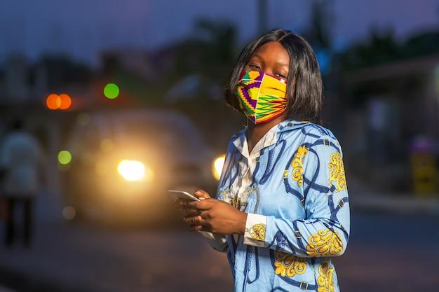 Junge afroamerikanische frau, die draußen eine bunte schutzmaske trägt