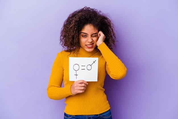 Junge afroamerikanische frau, die ein gleichstellungsplakat der geschlechter lokalisiert auf purpurroter wand hält, die ohren mit händen bedeckt