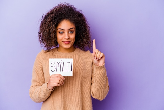 Junge afroamerikanische frau, die ein lächelnplakat lokalisiert auf lila wand zeigt, die nummer eins mit finger zeigt.