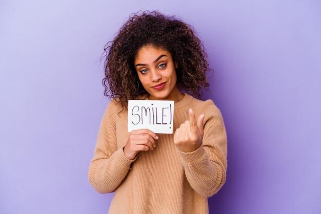Junge afroamerikanische frau, die ein lächelnplakat lokalisiert hält