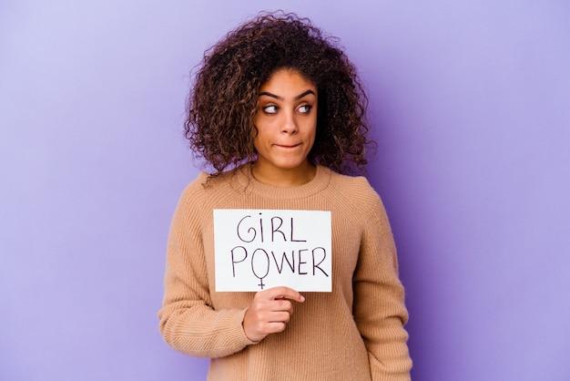 Junge afroamerikanische frau, die ein mädchen-kraftplakat hält, das auf purpurroter wand verwirrt ist, fühlt sich zweifelhaft und unsicher.