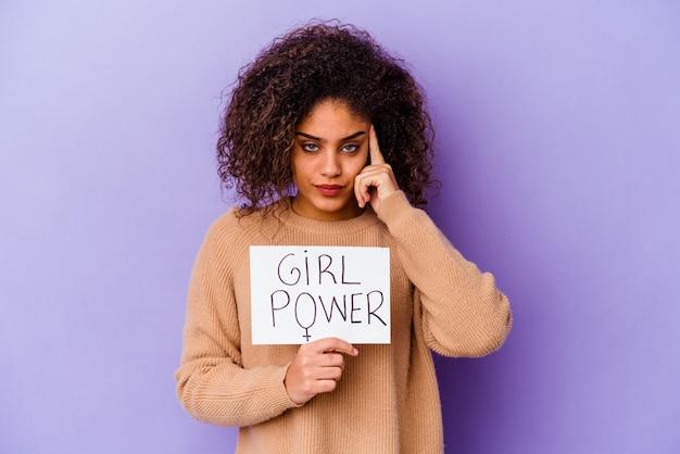 Junge afroamerikanische frau, die ein mädchen-kraftplakat lokalisiert auf lila wand zeigt tempel mit finger, denkend, konzentriert auf eine aufgabe.