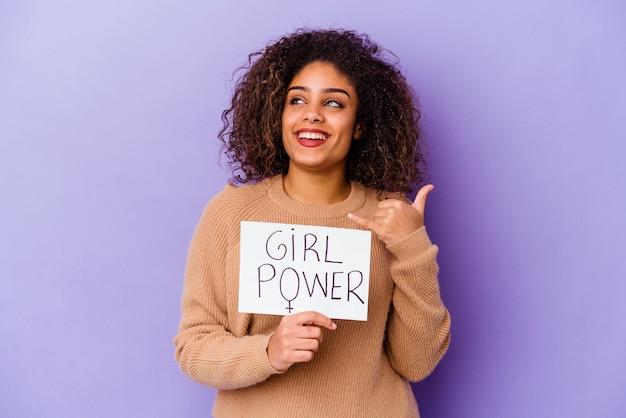 Junge afroamerikanische frau, die ein mädchen-kraftplakat lokalisiert auf purpur hält, das eine handy-anrufgeste mit den fingern zeigt.