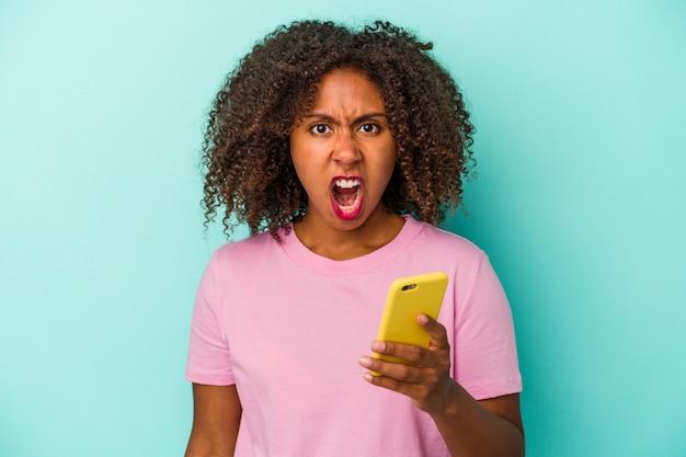 Junge afroamerikanische frau, die ein mobiltelefon auf blauem hintergrund isoliert hält und sehr wütend und aggressiv schreit.