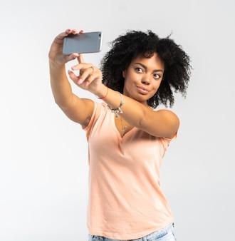 Junge afroamerikanische frau, die ein selfie nimmt