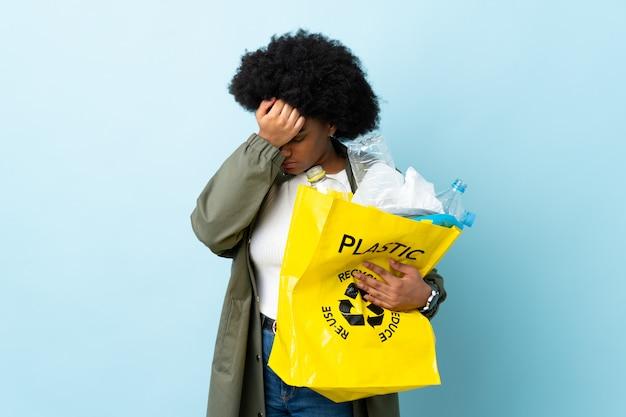 Junge afroamerikanische frau, die eine recycling-tasche auf bunter wand mit kopfschmerzen hält