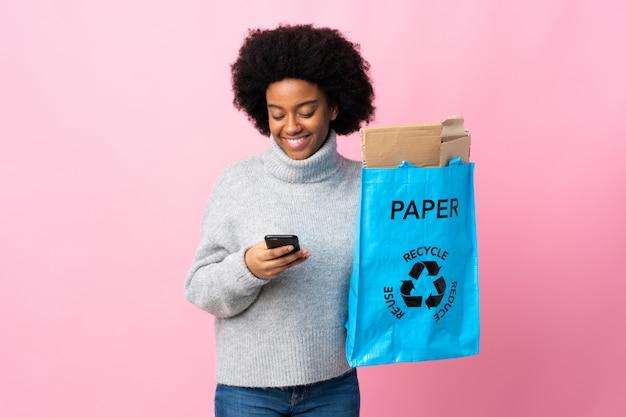Junge afroamerikanische frau, die eine recycling-tasche hält, die eine nachricht mit dem handy sendet