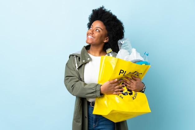 Junge afroamerikanische frau, die eine recycling-tasche lokalisiert auf buntem nachschlagen beim lächeln hält
