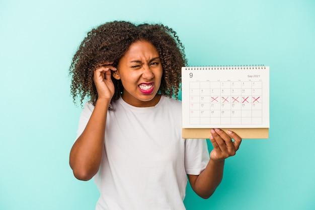 Junge afroamerikanische frau, die einen kalender auf blauem hintergrund isoliert hält und die ohren mit den händen bedeckt.