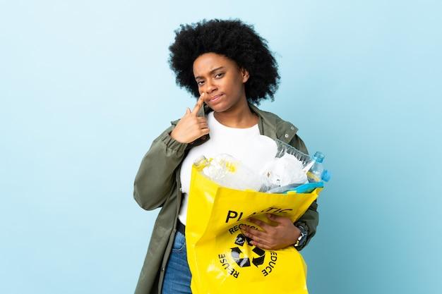 Junge afroamerikanische frau, die einen recyclingbeutel lokalisiert auf buntem zeigen etwas hält