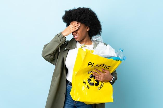 Junge afroamerikanische frau, die einen recyclingbeutel mit kopfschmerzen hält