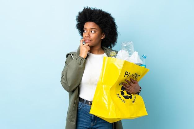 Junge afroamerikanische frau, die einen recyclingbeutel nervös und ängstlich hält