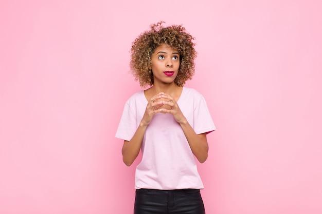 Junge afroamerikanische frau, die entwirft und verschwört, verschlagene tricks und betrüger denkt, gerissen und verrät gegen rosa wand