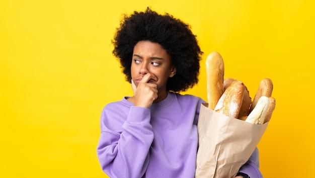 Junge afroamerikanische frau, die etwas brot auf gelber wand kauft, die zweifel und mit verwirrendem gesichtsausdruck hat