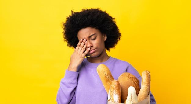Junge afroamerikanische frau, die etwas brot auf gelber wand mit kopfschmerzen kauft