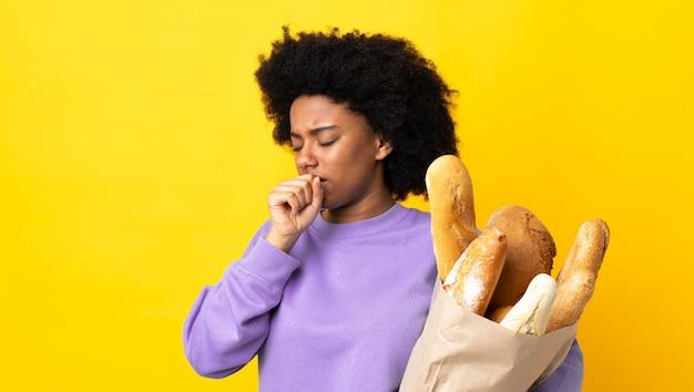 Junge afroamerikanische frau, die etwas brot kauft, das auf gelbe wand isoliert wird, die viel hustet