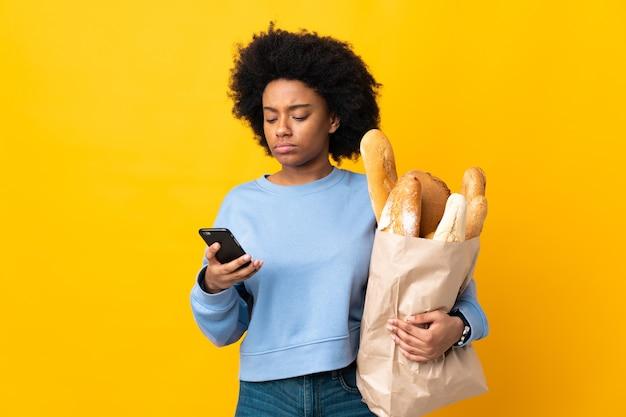 Junge afroamerikanische frau, die etwas brot kauft, das auf gelbem denken isoliert wird und eine nachricht sendet