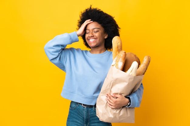 Junge afroamerikanische frau, die etwas brot lokalisiert auf gelbem hintergrund lachend kauft