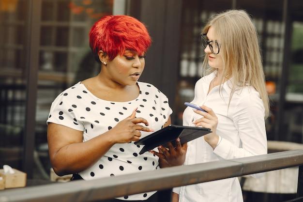 Junge afroamerikanische frau, die in einem büro arbeitet. dame in einer weißen bluse. kaukasische frau mit ihrem afrikanischen kollegen.