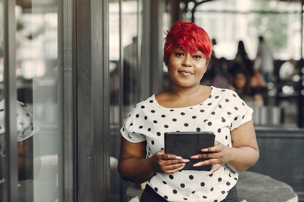 Junge afroamerikanische frau, die in einem büro arbeitet. dame in einer weißen bluse.