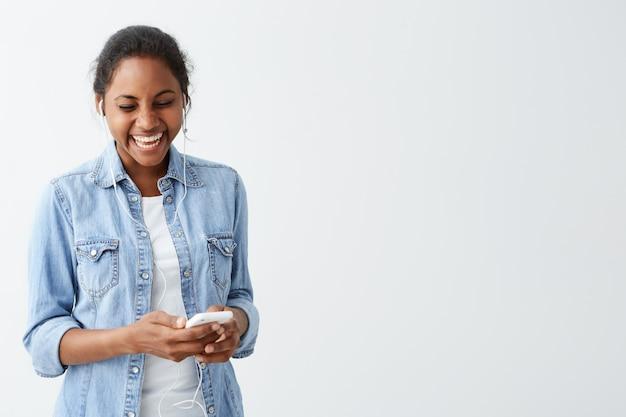 Junge afroamerikanische frau, die lacht und glücklichen ausdruck hat, während sie nachrichten von ihren freunden liest, die über weißer wand isoliert werden. menschen- und technologiekonzept