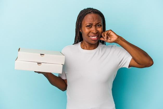 Junge afroamerikanische frau, die pizzas auf blauem hintergrund isoliert hält und die ohren mit den händen bedeckt.