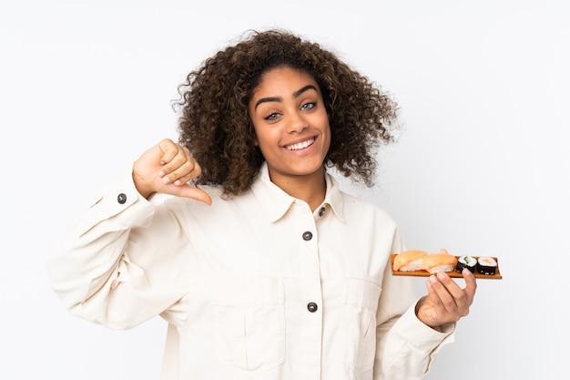 Junge afroamerikanische frau, die sushi auf weißer wand hält, die auf sich selbst zeigt