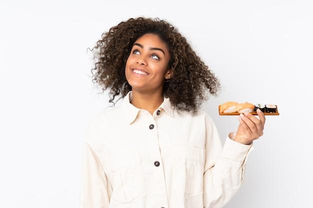 Junge afroamerikanische frau, die sushi lokalisiert auf weißem raum hält, während sie lächelnd hält