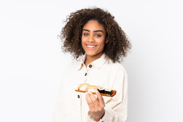 Junge afroamerikanische frau, die sushi lokalisiert auf weißem raum mit glücklichem ausdruck hält