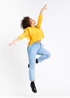 Junge afroamerikanische frau, die über weiße wand tanzt