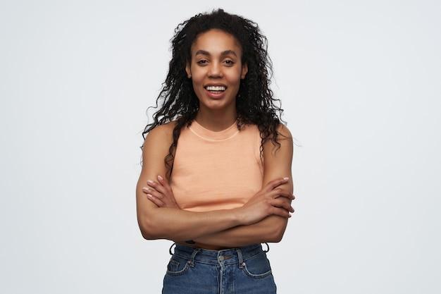 Junge afroamerikanische frau, die weiß steht und mit einem breiten lächeln schaut