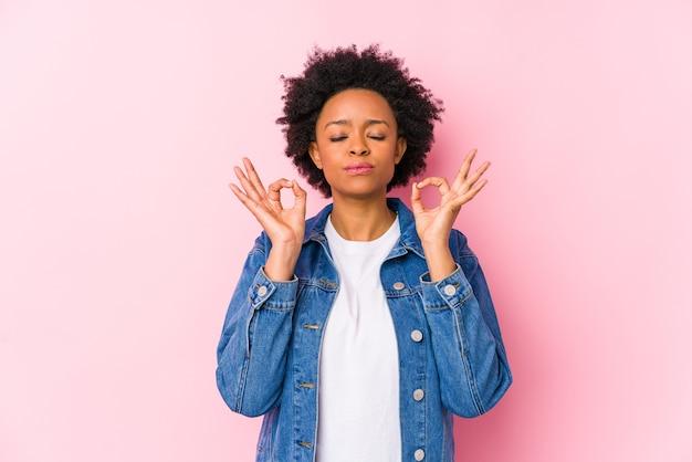 Junge afroamerikanische frau gegen eine rosa hintergrundgruppe isoliert entspannt sich nach hartem arbeitstag, sie führt yoga durch.