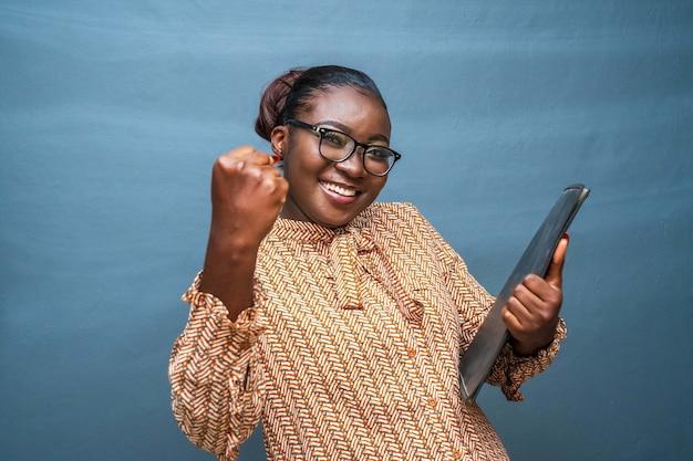 Junge afroamerikanische frau gestikuliert mit ihrem faust - weibliches ermächtigungskonzept