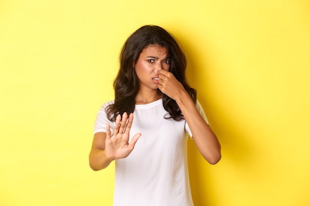 Junge afroamerikanische frau im weißen t-shirt, schloss die nase, sah angewidert aus und bittet darum, weg zu bleiben, mag keinen schlechten geruch, steht auf gelbem hintergrund.