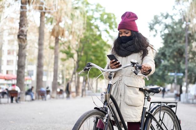 Junge afroamerikanische frau in einer stadt, die ein smartphone auf ihrem fahrrad verwendet. sie trägt winterkleidung mit schal und wollmütze.