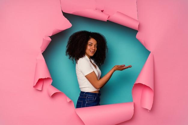 Junge afroamerikanische frau in zerrissenem papier lokalisiert auf blau, das einen kopienraum auf einer handfläche hält.
