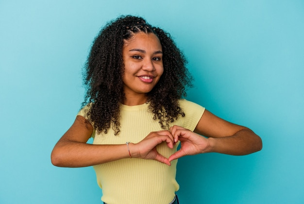 Junge afroamerikanische frau isoliert auf blauem hintergrund lächelt und zeigt eine herzform mit den händen.