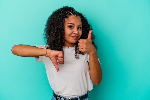 Junge afroamerikanische frau isoliert auf blauem hintergrund mit daumen nach oben und daumen nach unten, schwieriges konzept zu wählen