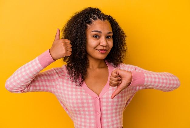 Junge afroamerikanische frau isoliert auf gelbem hintergrund mit daumen nach oben und daumen nach unten, schwieriges konzept zu wählen