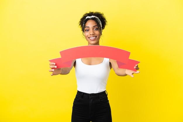 Junge afroamerikanische frau isoliert auf gelbem hintergrund mit einem leeren plakat