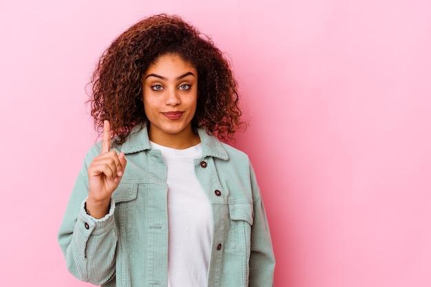 Junge afroamerikanische frau isoliert auf rosa hintergrund, die nummer eins mit dem finger zeigt.