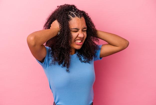 Junge afroamerikanische frau isoliert auf rosa hintergrund, die ohren mit den händen bedeckt.